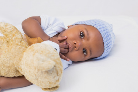 babygro: Adorable baby boy with teddy at home in the living room