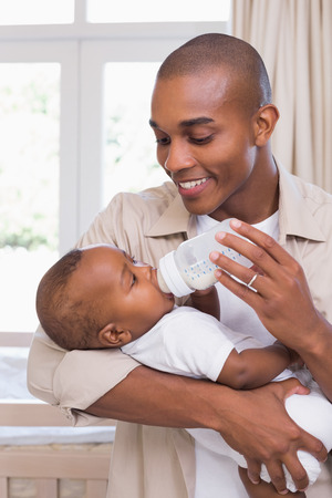 Happy father feeding his baby boy a bottle at home in the bedroom photo