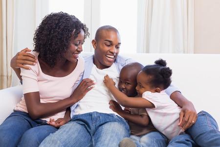 ni�os felices: Familia feliz sentado en el sof� juntos en casa en la sala de estar Foto de archivo