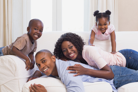 african american mother and daughter: Happy family posing on the couch together at home in the living room