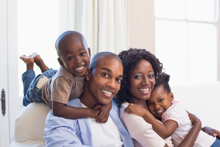 Happy family posing on the couch together at home in the living room