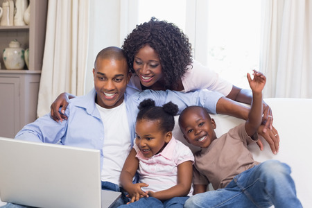 Happy family on the couch together using laptop at home in the living room photo