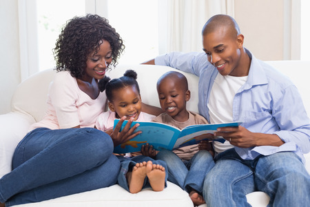 reading: Happy family on the couch reading storybook at home in the living room Stock Photo
