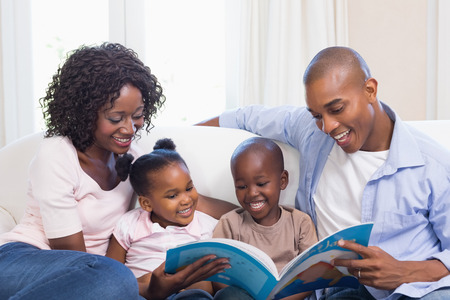 child: Happy family on the couch reading storybook at home in the living room Stock Photo