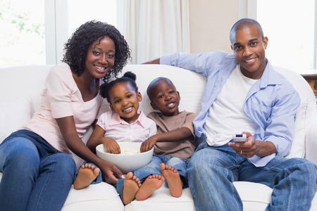 television remote: Happy family watching television together at home in the living room