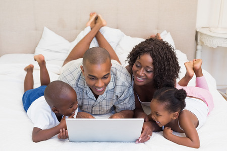 Happy family using laptop together on bed at home in the bedroom photo