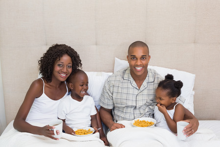 Happy family having breakfast in bed together in the morning at home in the bedroom photo