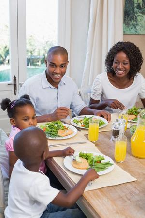 food woman: Famille heureux en appr�ciant un repas sain ensemble � la maison dans la cuisine