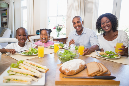Happy family enjoying a healthy meal together at home in the kitchen photo