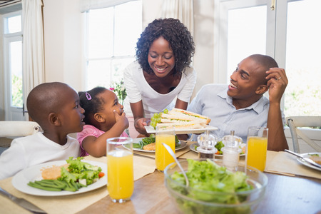 healthy eating: Happy family enjoying a healthy meal together at home in the kitchen