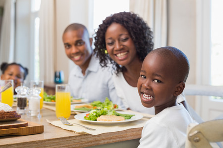 Happy family smiling at camera at lunch at home in the kitchen