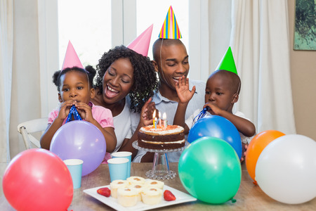 adult birthday: Happy family celebrating a birthday together at table at home in the kitchen