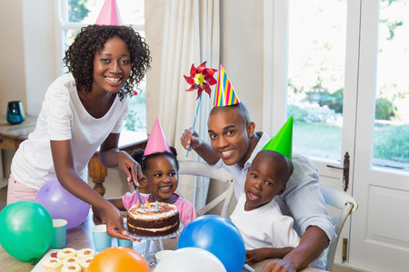 party hat: Happy family celebrating a birthday together at table at home in the kitchen