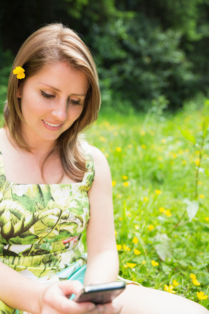 Relaxed young woman text messaging in field photo