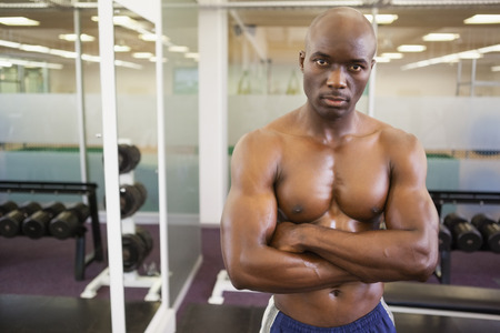 Portrait of a serious shirtless muscular man standing in gym photo
