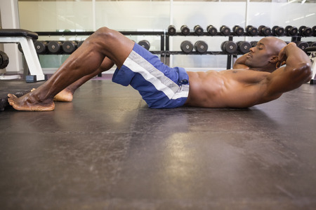 Full length side view of muscular man doing abdominal crunches in gym photo
