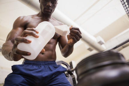 scooping: Shirtless body builder scooping up protein powder in gym Stock Photo