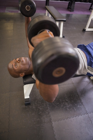 Young muscular man exercising with dumbbells in gym photo