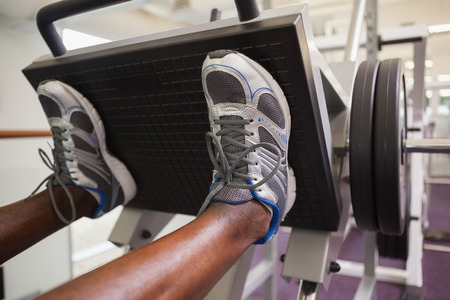 Close up of male weightlifter doing leg presses in gym photo