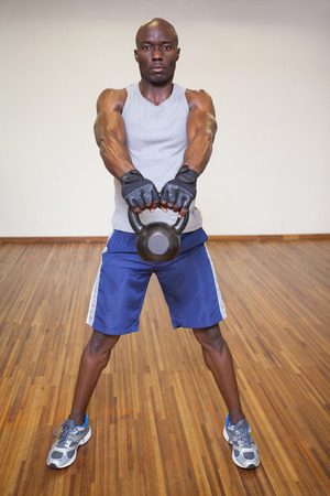 Full length of a young muscular man exercising with kettle bell in gym photo
