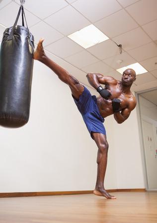 Full length of a shirtless muscular boxer kicking punching bag in gym