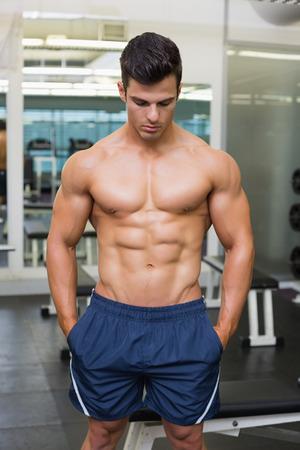shirtless: Hombre musculoso sin camisa mirando hacia abajo en el gimnasio
