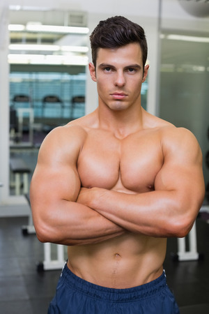 Serious shirtless young muscular man standing in gym photo