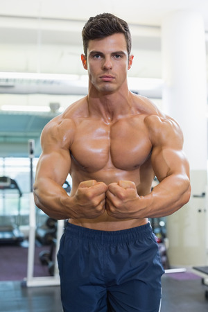 clenching: Portrait of a shirtless muscular man flexing muscles in gym Stock Photo