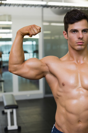 clenching: Close-up of muscular man flexing muscles in gym Stock Photo