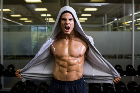 Portrait of a muscular young man shouting in health club photo