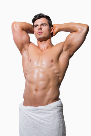 shirtless man: Portrait of a shirtless muscular man wrapped in white towel over white background