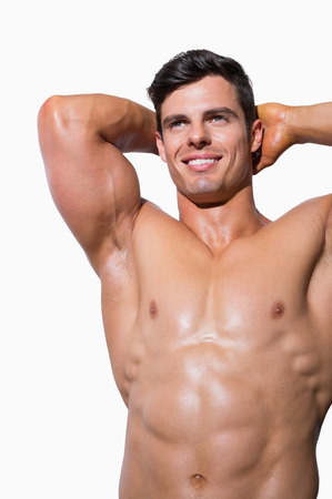 Portrait of a smiling shirtless muscular man over white background photo