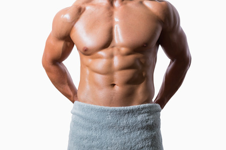 Mid section of a shirtless muscular man wrapped in white towel over white background Stock Photo