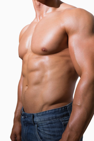 Mid section of a shirtless muscular man over white background photo