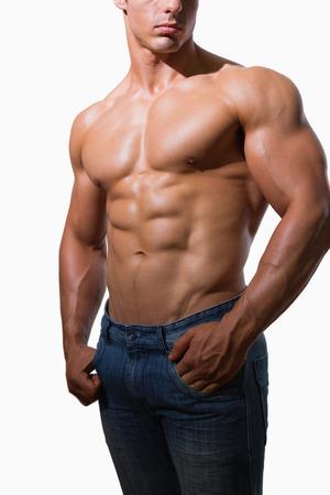 白い背景の上の上半身裸の筋肉男の中間セクション