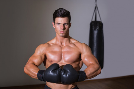 Portrait of a shirtless muscular boxer standing in health club photo