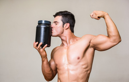 Shirtless muscular man kissing nutritional supplement over white background photo