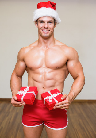 Portrait of shirtless macho man in santa hat holding gifts photo