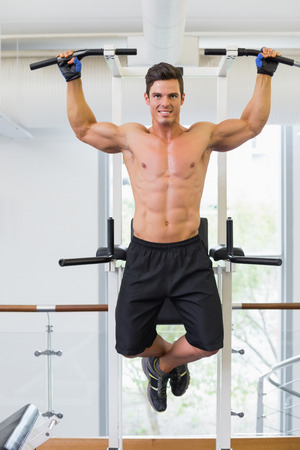 body builder: Shirtless male body builder doing pull ups at the gym