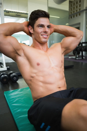 Smiling young muscular man doing abdominal crunches in gym photo