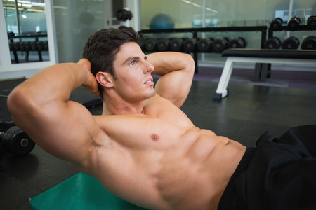 Side view of muscular man doing abdominal crunches in gym photo
