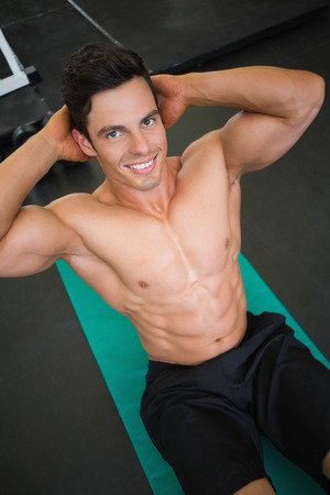 High angle view of muscular man doing abdominal crunches in gym photo