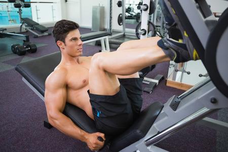 piernas hombre: Vista lateral del weightlifter haciendo press de piernas masculinas en el gimnasio