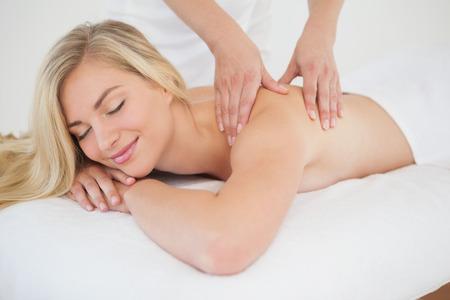 Hübsche Blondine genießt eine Massage im Wellnessbereich