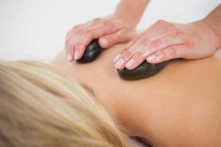 masaje: Hermosa rubia disfrutando de un masaje con piedras calientes en el spa de salud