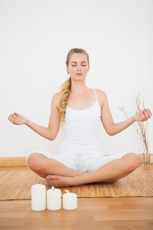 house of prayer: Peaceful blonde sitting in lotus pose on bamboo mat at home against a white wall