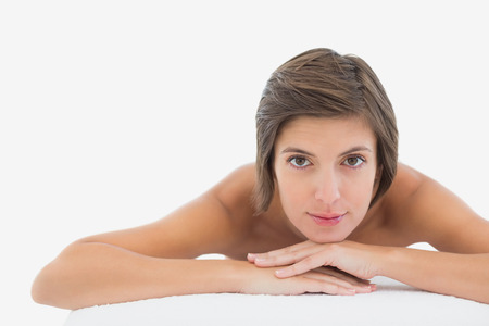 Close up portrait of a beautiful young woman on massage table over white background photo