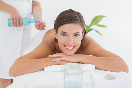 body care: Attractive young woman getting massage oil on her back at spa center