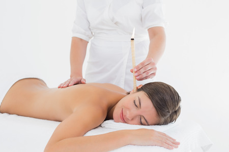 Side view of a beautiful young woman receiving ear candle treatment at spa center photo