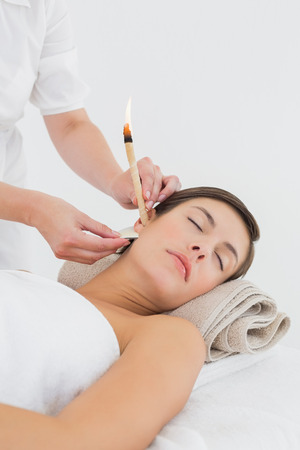 Close up of a beautiful young woman receiving ear candle treatment at spa center photo